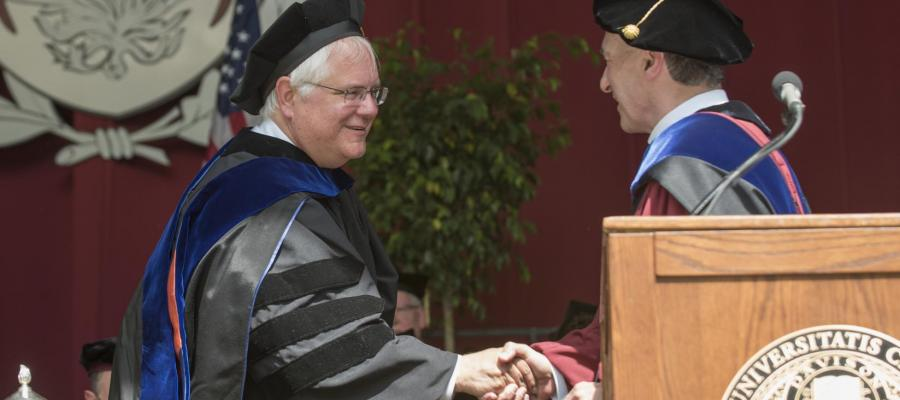 Two men in graduation regalia shake hands at convocation
